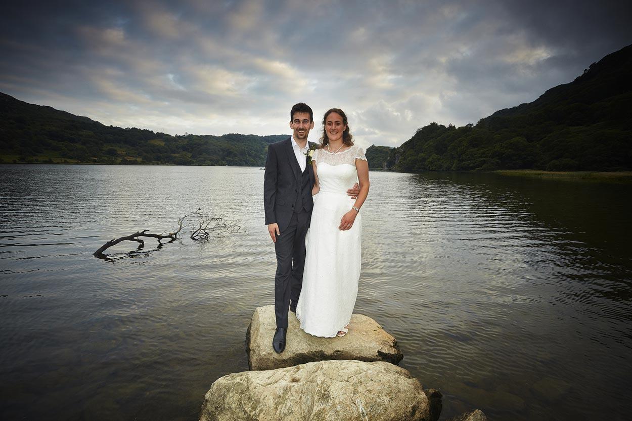 bride and groom by llyn gwynant after their wedding llyn