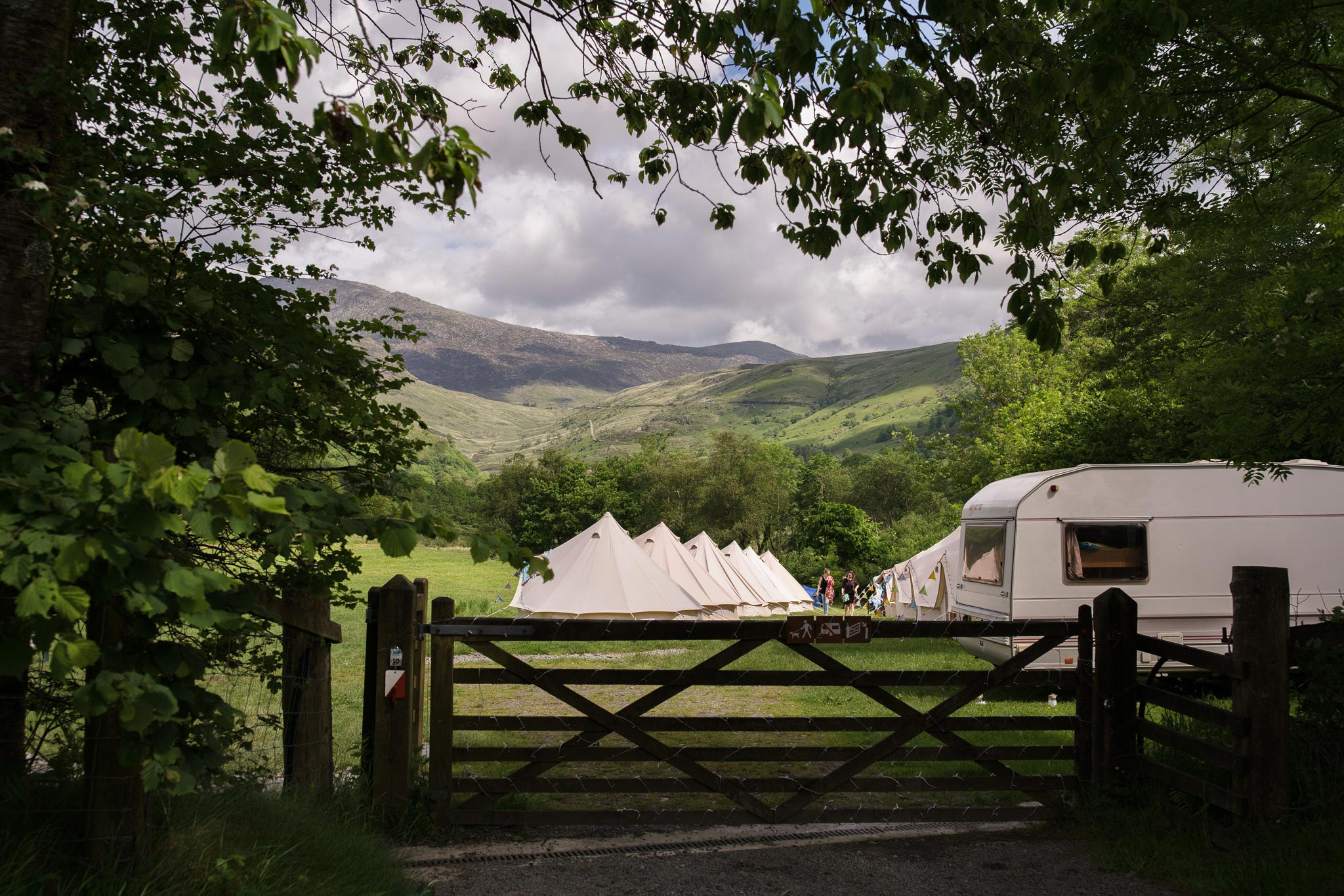 glamping tents and caravans in barn field for a wedding