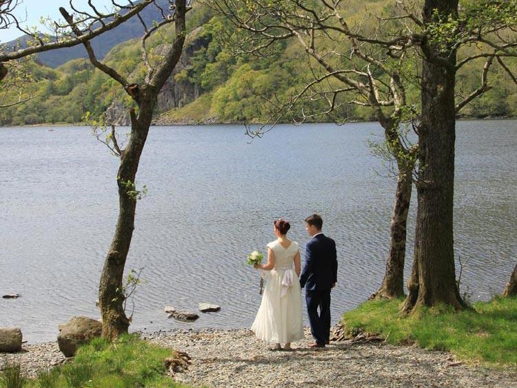 a bride and groom on the shores of llyn gwynant llyn