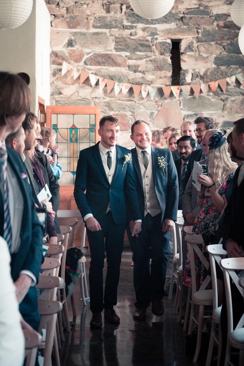 two grooms enter big barn for their wedding llyn gwynant