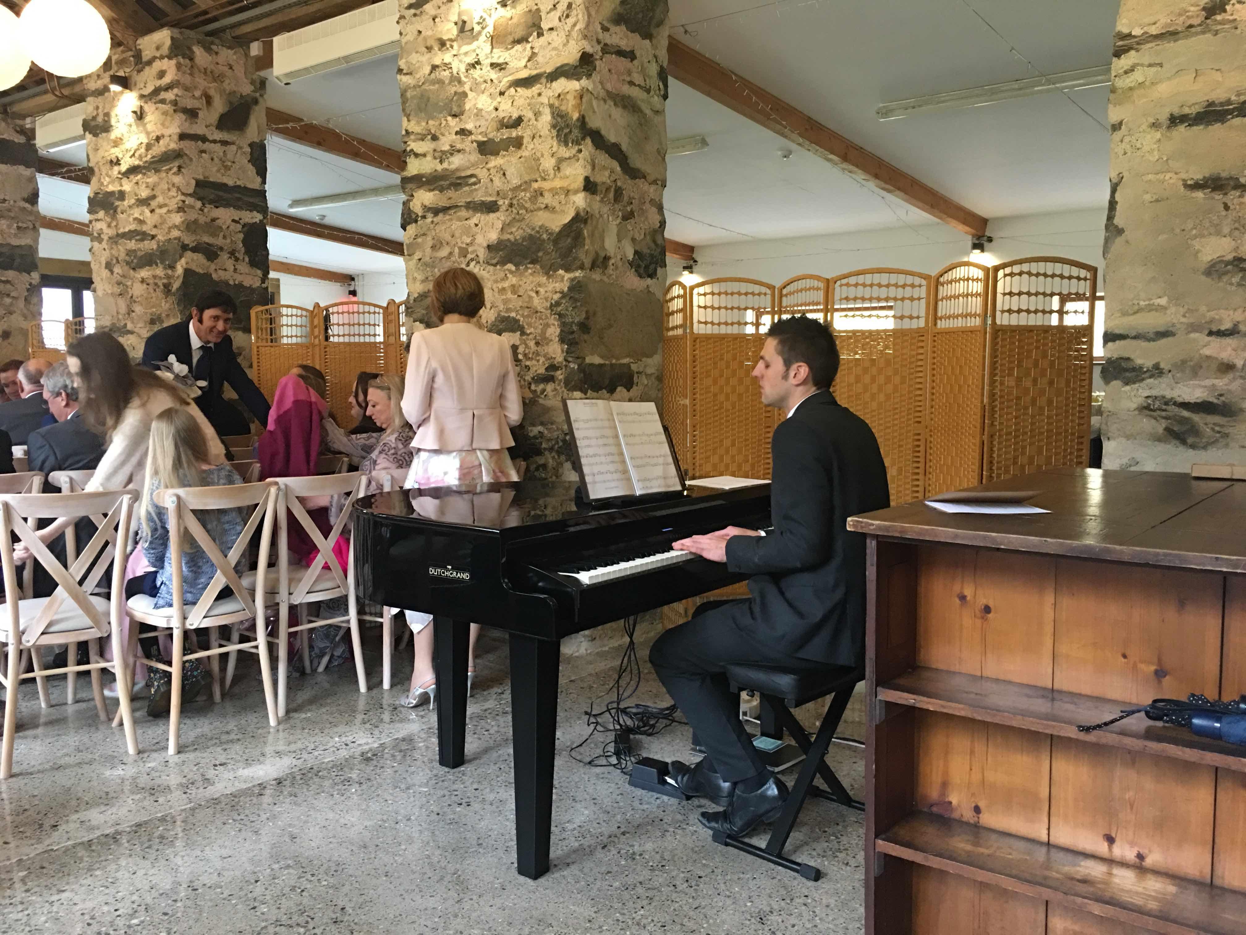 pianist in big barn before a wedding ceremony llyn
